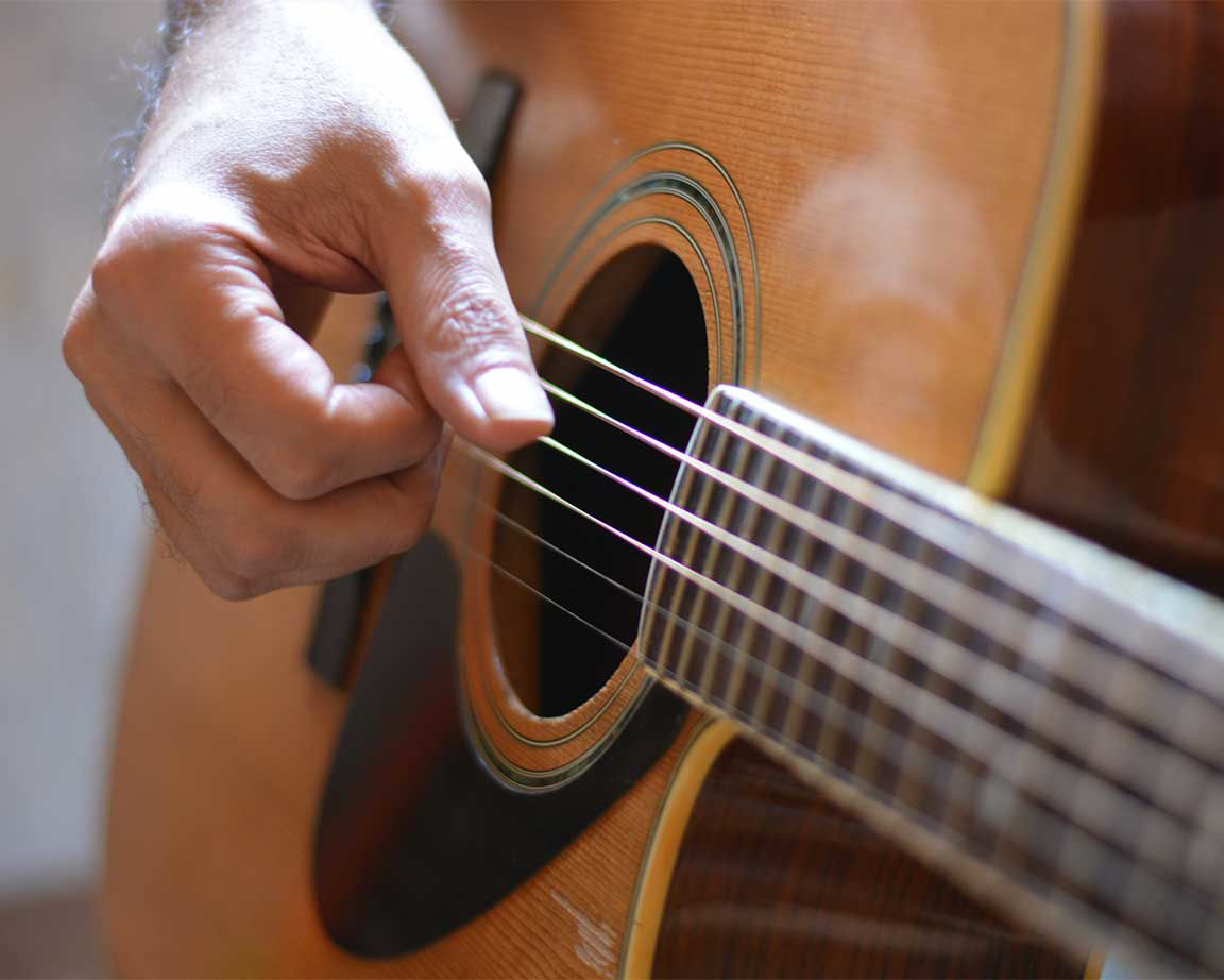 close up of fingers struming acoustic guitar