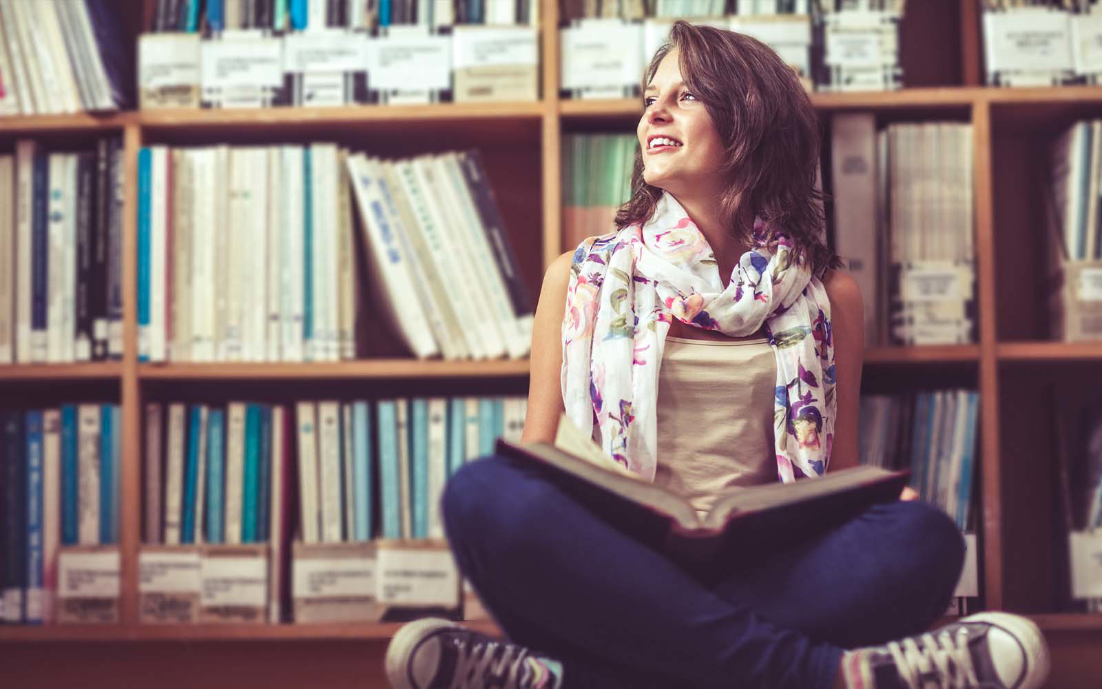 woman sitting on floor in library stacks
