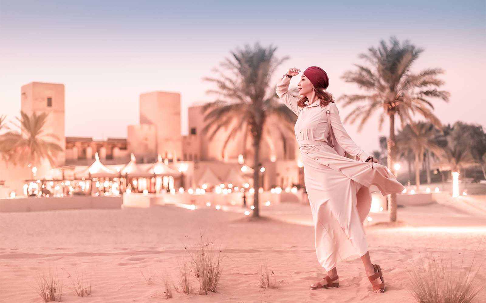 woman looking in distance with desert city behind her